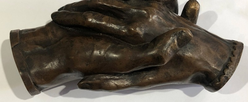sculpture of two hands clasping each other